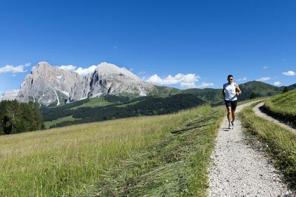 Uomo che corre sentiero Alpe di Siusi