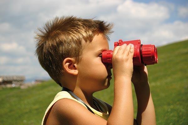 bambino con cannocchiale guarda panorama dolomiti