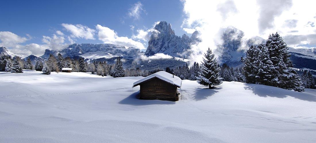vista romantica di una baracca di legno innevata alpe di siusi inverno
